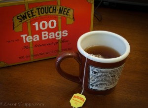Image of the Swee-Touch-Nee Tea Pacakge with a Cup Brewing in the Foreground